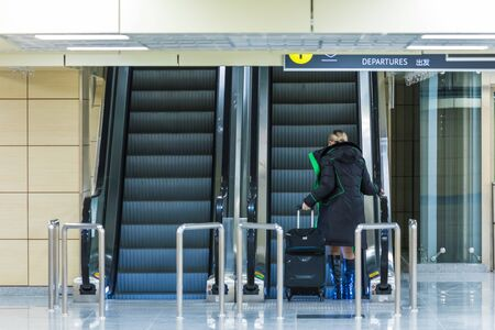 Woman on the escalator with luggage