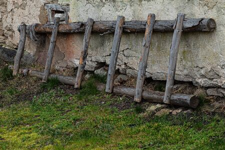 Ladder leaned on old stone building wall