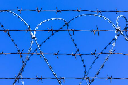 Barbed wire silhouette on background of blue sky