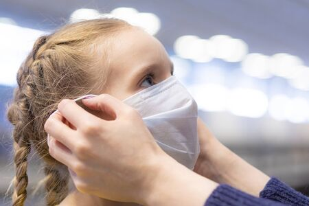 Mother hands dressing protection mask on girl