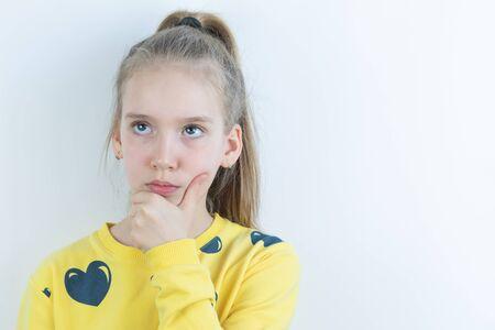 Girl in yellow sweater in thoughtful or dreamy pose