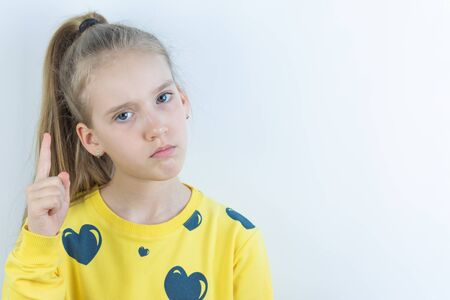 Girl in yellow sweater holding her forefinger up