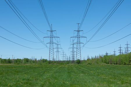 Towers of electric main in the countryside field