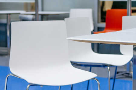 common room: corner of table and white plastic chair in common room in the open space office