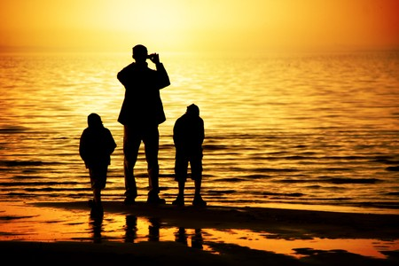 Silhouettes of father and two sons by the ocean looking to the sunset Stock Photo - 7245391