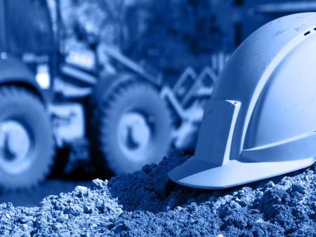 health safety: Cascos en el sitio de construcci�n, la excavadora en el fondo; tono azul  Foto de archivo