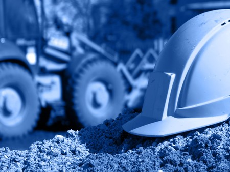 health and safety: Hard hat on the construction site, excavator on the background; blue hue