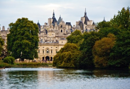 Scenic view over lake in St. Jamess Park with historic building in background, London, England photo