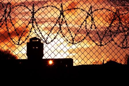 barbed wires: Sun en la configuraci�n de cielo naranja sobre el patio de la prisi�n  Foto de archivo