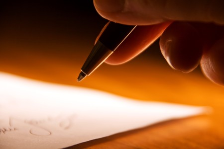 contractual: fingers of a hand holding an ink pen, about to sign a contract Stock Photo