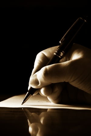 Hand writing a note on a sheet of paper with a pen photo