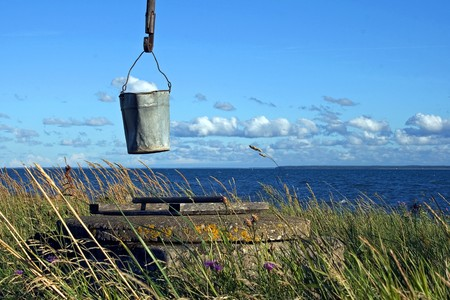 Sweep well and bucket on the sea shore photo