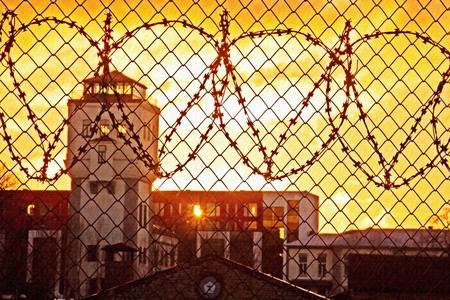 prison fence: Old abandoned prison facilities behind wired fence; sun shining through building; textured background