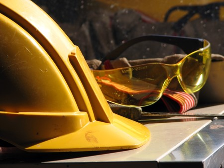 Yellow hard hat and yellow goggles on the table Stock Photo - 7399097