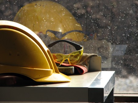 health and safety: Yellow hard hat and yellow goggles on the table by the window Stock Photo