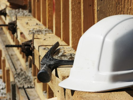 White hard hat and hammer on the wooden construction frame