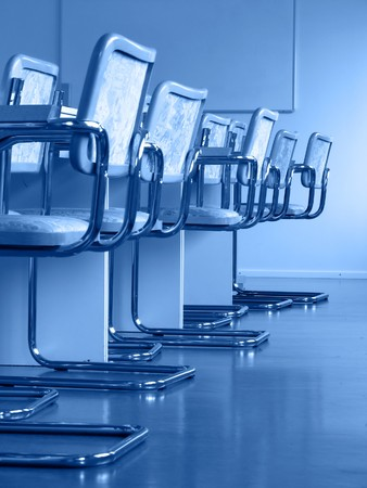 Chairs in the conference room; blackboard on the background; blue tint photo