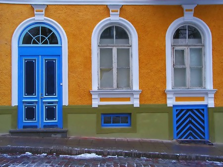 Yellow house with blue door, two white window and green basement by the grey street photo