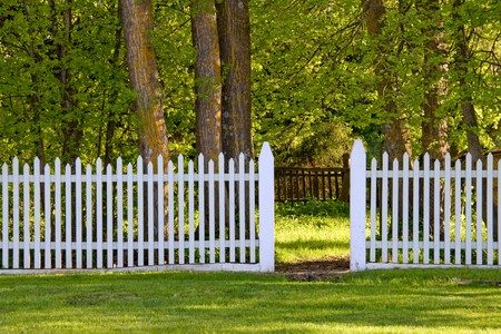 A white picket fence with an open gate to the park