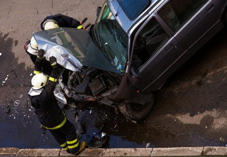 damages: Firemen at traffic accident site, checking car, holding engine hood open