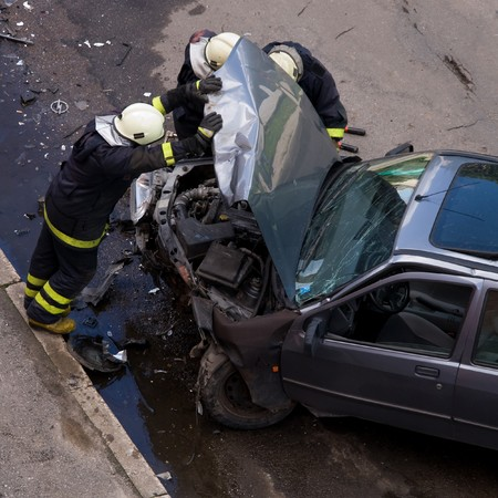 Firemen at traffic accident site, checking car, holding engine hood open photo