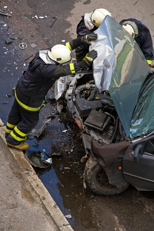 Firemen at traffic accident site, checking car, holding engine hood open Stock Photo - 7435931
