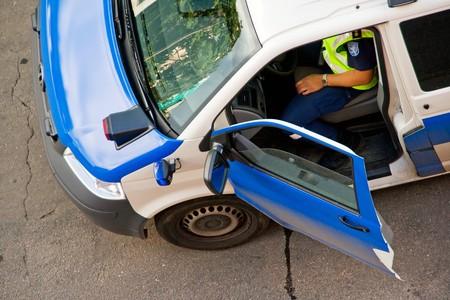 Policeman sitting in police car, door open photo