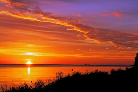 puesta de sol: Hermosa puesta de sol ardiente en la orilla del mar