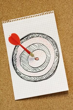 Red arrow hitting bulls eye of hand drawn dartboard photo