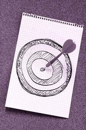 Arrow hitting bulls eye of hand drawn dartboard; violet tint photo