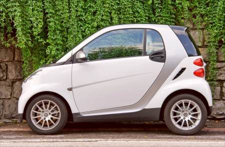 Small city car by the stone wall photo