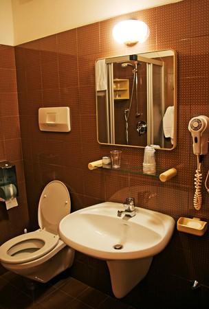 productos de aseo: Ba�o con lavabo, inodoro, art�culos de tocador y espejo en la pared de baldosas cer�mica  Foto de archivo