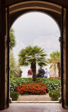 Entrance into beautiful garden with palms and flowers by lake garda, italy photo