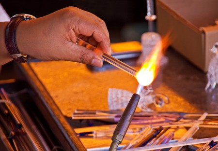 glassblower: A glassblower at work, focus on his hands melting glass with a gas burner Stock Photo