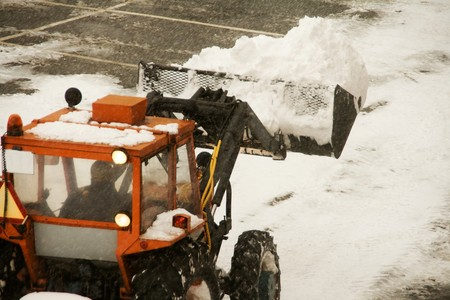 A snow plow clearing a parking lot photo