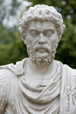 White stone sculpture of ancient Roman or Greek man with curly hair and beard photo