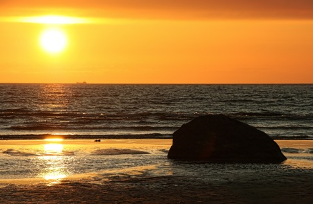 Colorful orange sunset by the sea, stone rock and foamy waves in the front Stock Photo - 8519956