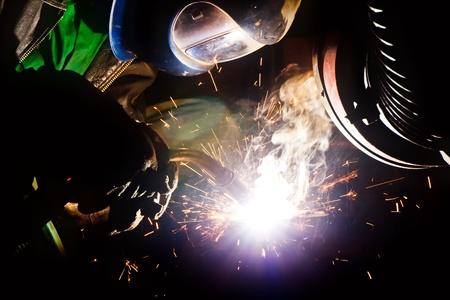 Welder with welding helmet working hard, sparks and smoke around him photo