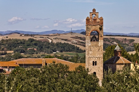 Romanesque basilica of Sant Agata in Asciano and Crete Senesi landscapes on the background, Tuscany, Italy photo
