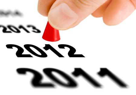 the next step: Mano con il pezzo gioco prendendo il passo successivo dal numero dell'anno 2011 per il prossimo anno 2012 Archivio Fotografico