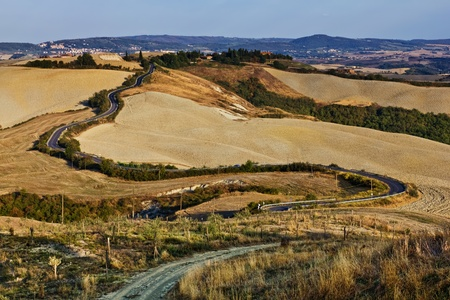 sinuous: Sinuous roads on the clay hills of Crete Senesi in Tuscany, Italy