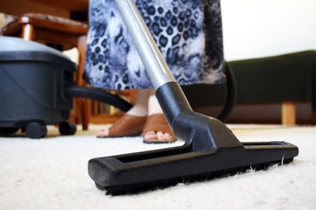 Woman cleaning house with vacuum cleaner photo