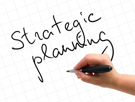 Illustration of the hand with a pen writing STRATEGIC PLANNING on the white paper background illustration