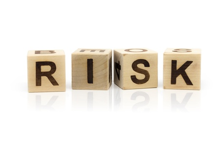 Photo of wooden letter blocks forming the word Risk on the white background with reflection photo