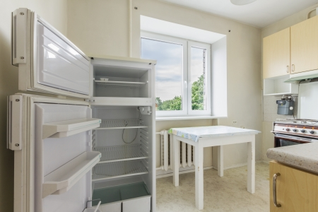 Interior photo of the small empty kitchen with open refrigerator, kitchen table, cabinets and stove photo