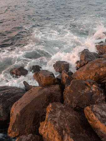 Turquoise sea wave beats on the rocks. Beautiful splashes fly away from stones. Sunrise atmosphere. 免版税图像