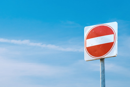 A square red sign with a white bar indicating NO ENTRY on a grey metal post against a blue cloudy sky.