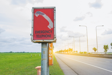 Emergency booth phone with green yard and blue sky background