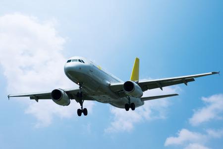 White passenger plane flying on blue sky background