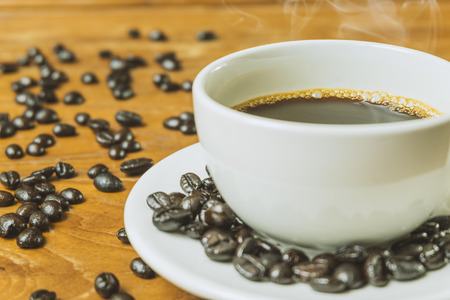 textured wall: Black coffee in white cup and coffee bean on wooden table Stock Photo